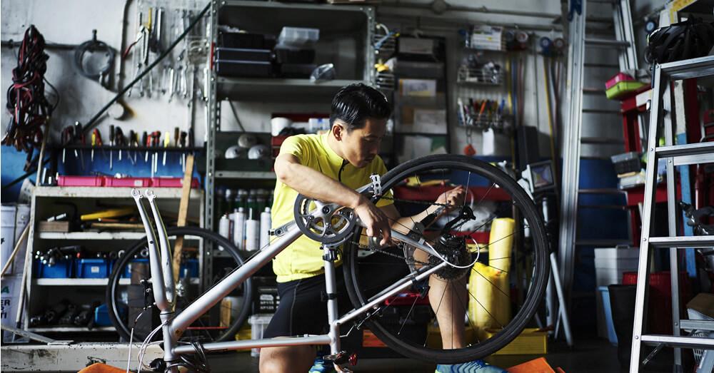 ロードバイクのメンテナンスをする男性の写真