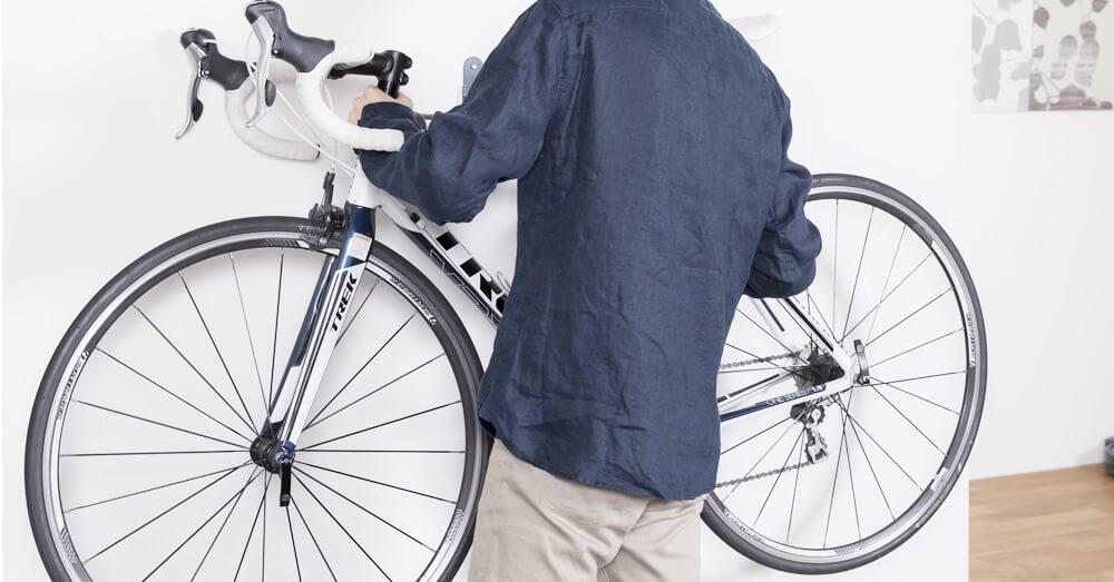 ロードバイクを運び込む男性の写真