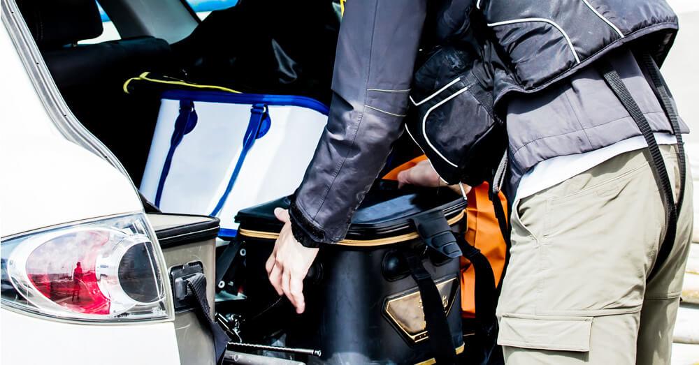 釣り具を車に運び込む男性の写真